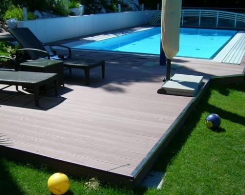 терраса с басейном. Сам бассейн небольшой, два шизлонга. Светлый деревянный паркет становиться границей между купальной зоной и травой.
